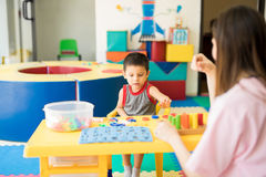 Boy learning the alphabet. Little boy getting language therapy and learning the alphabet in a rehabilitation and child development center Stock Images