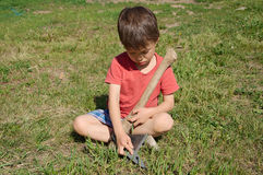 Boy learning in ax blade sharpening Stock Photography