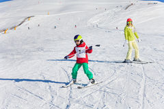 Boy learning downhill skiing with instructor stock photos