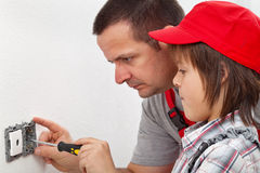 Boy learning how to fix an electrical wall fixture. Assisting his father Royalty Free Stock Images