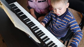 Boy learning how to the play piano stock footage