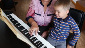 Boy learning how to the play piano stock video footage