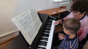 Boy learning how to the play piano stock video