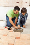 Boy learning how to spread adhesive for ceramic floor tiles Stock Photo