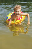 Boy learning how to swim with a floating ring Royalty Free Stock Photography