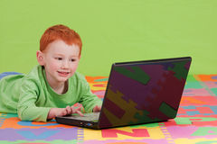 Boy learning with notebook computer. Boy using notebook computer on alphabet letters mat Royalty Free Stock Images