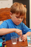 Boy learning science. A seven year old boy does a science experiment. He is mixing powders in a cup. He is wearing a blue tee shirt and is paying close Stock Image