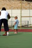 Boy learning tennis. On a court Stock Photo