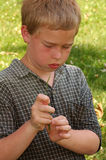 Boy learning to blow the grass whistle. Positioning a blade of grass between fingers Stock Images