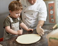Boy learning to cook  pizza Stock Photography
