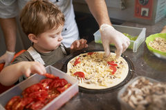 Boy learning to cook pizza with  chef Royalty Free Stock Photo