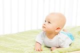Boy learning to crawl in his crib Royalty Free Stock Photo