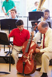 Boy Learning To Play Cello In High School Orchestra. Sitting Down Next To Teacher Royalty Free Stock Image