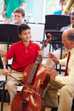 Boy Learning To Play Cello In High School Orchestra. Smiling At Teacher Stock Photo