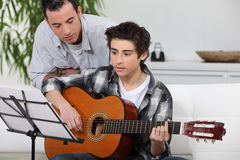 Boy learning to play the guitar. Adolescent boy learning to play the guitar Royalty Free Stock Photos