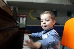 Boy learning to play the piano Stock Image