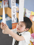 Boy Learning To Read From Hanging Paper Strip In Class Stock Images