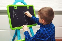 The boy is learning to read and write . The child learns the alphabet. Initial education royalty free stock photos