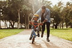 Father teaching his son cycling at park. Boy learning to ride a bicycle with his father in park. Father teaching his son cycling at park stock images