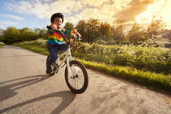 Boy learning to ride his bike stock photos