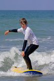 Boy learning to surf 1. A boy in a wet suit learning to surf.  This photo is taken on Borth beach in the west of Wales Stock Images