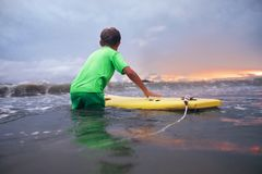 Boy learning to surf in ocean waves at sunset time Stock Photos