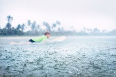 Boy learning to surf under the tropical rain Stock Photo