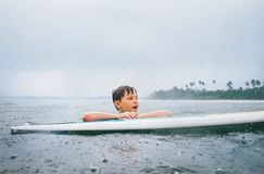 Boy learning to surf under the tropical rain Royalty Free Stock Image