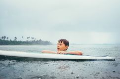 Boy learning to surf under the tropical rain. Surf school education concept image stock image