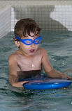 Boy learning to swim. A boy learning to use goggles and a floater Royalty Free Stock Photos