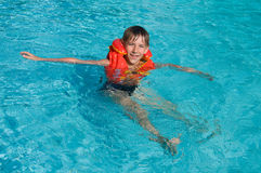 Boy learning to swim. Boy in life jacket is learning to swim in the swimming pool Royalty Free Stock Photography