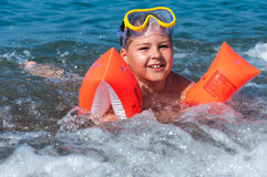 Boy learning to swim with oversleeves Royalty Free Stock Photography
