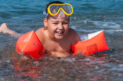 Boy learning to swim with oversleeves Stock Photo