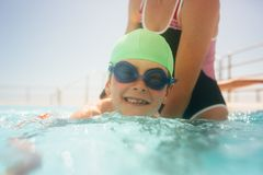 Boy learning to swim in a pool. Cute boy wearing swim cap and goggles learning to swim with a woman`s help in a pool. Boy having swimming lesson in the pool with stock photo