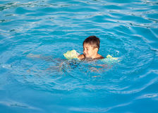 Boy learning to swim in the pool Stock Photography