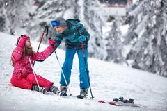 Boy learning young girl skiing on snow. And having fun Royalty Free Stock Photos