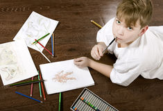 Boy learns and develops draws Royalty Free Stock Photography