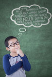 Boy learns foreign vocabulary. Photo of a cute little boy wearing casual clothes and studying foreign vocabulary in the classroom Stock Images