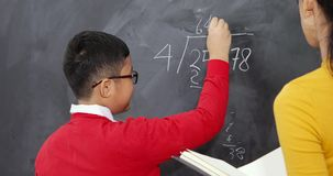 Boy learns math with his teacher. Male elementary school student learns math with his female teacher while writing on chalkboard. Shot in 4k resolution stock video