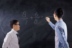 Boy learns math lesson in class. Little boy standing in the classroom while learning math lesson with his teacher Stock Photos