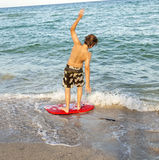 Boy learns surfing at the beach Royalty Free Stock Photography