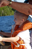 Boy learns to drive the boat. This cute boy pays close attention as his grandpa tells him what to do to drive the boat Stock Image
