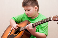 Boy learns to play the guitar Stock Image