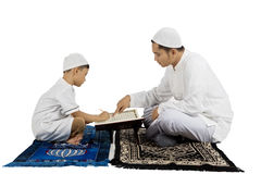 Boy learns to read Quran with father Stock Photos
