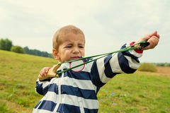 Boy learns to shoot a slingshot Stock Photo