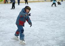 The boy learns to skate on ice. royalty free stock images