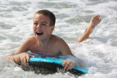 Boy learns to surf in the sea Royalty Free Stock Photography