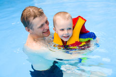 Boy learns to swim in pool with father Stock Photography