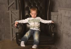 Boy in leather chair Stock Photography