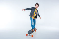 Boy in leather jacket riding skateboard on grey Stock Photography